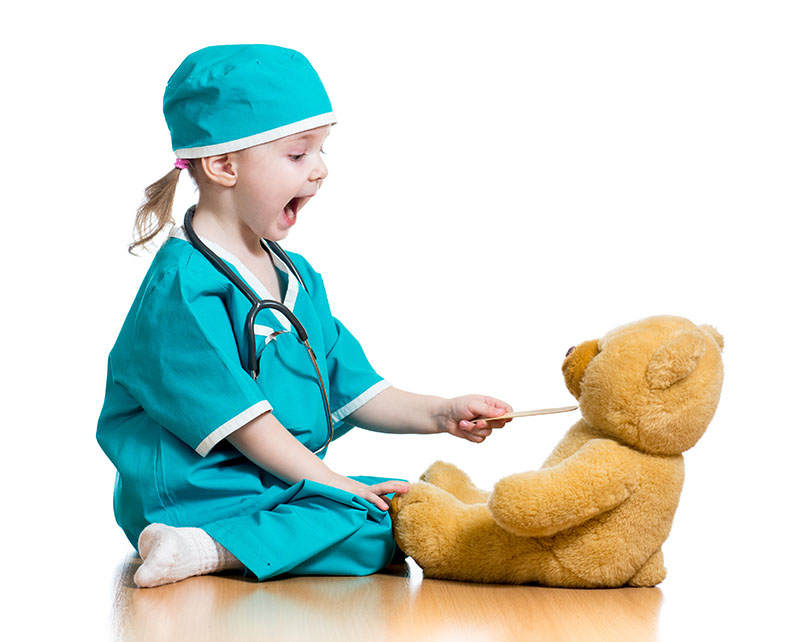 child dressed up as a surgeon looking in teddy bear's throat